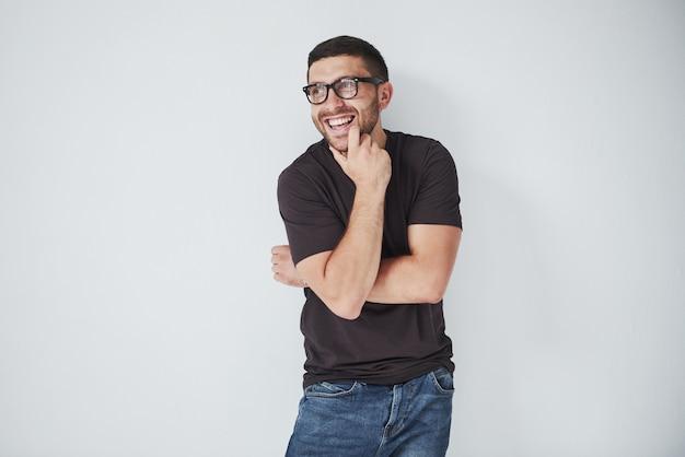 Portret van een knappe jonge mens die op iets denkt, dat op wit wordt geïsoleerd Gratis Foto
