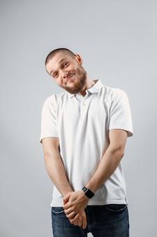 Portret van een knappe jonge verlegen man in een wit t-shirt op grijs