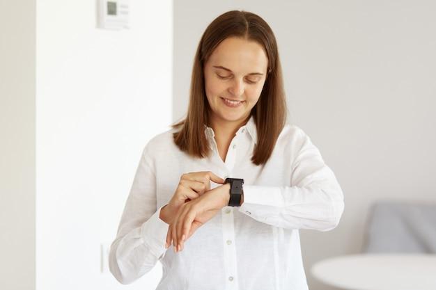 Portret van een knappe jonge volwassen vrouw die een wit overhemd in casual stijl draagt, haar polshorloge gebruikt, naar het scherm van een smartphone kijkt en binnen in een lichte kamer poseert.