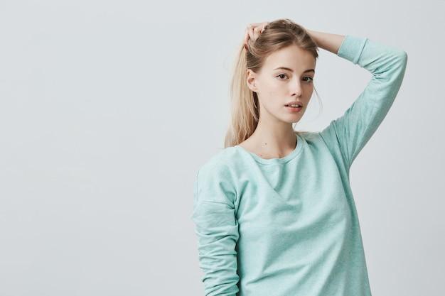 Portret van een knappe jonge vrouw met een ovaal gezicht, donkere ogen en blond steil haar, gekleed in een blauwe casual trui, peinzend en vol vertrouwen met haar haar spelend