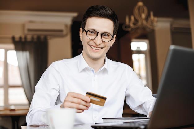 Portret van een knappe jonge zakenman die camera bekijkt die lacht terwijl hij een gouden creditcard aan een bureau houdt die aan zijn laptop werkt.
