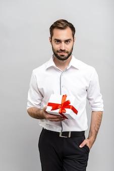 Portret van een knappe jonge zakenman met een wit overhemd en stropdas die geïsoleerd over een grijze muur staat en een geschenkdoos toont