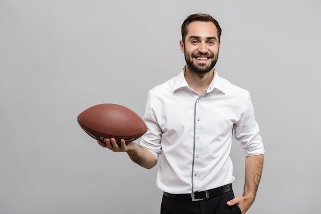 Portret van een knappe jonge zakenman met een wit overhemd en stropdas die geïsoleerd over een grijze muur staat en rugbybal vasthoudt