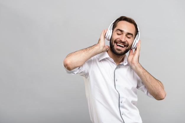 Portret van een knappe jonge zakenman met een wit overhemd en stropdas, geïsoleerd over een grijze muur, luisterend naar muziek met een draadloze koptelefoon