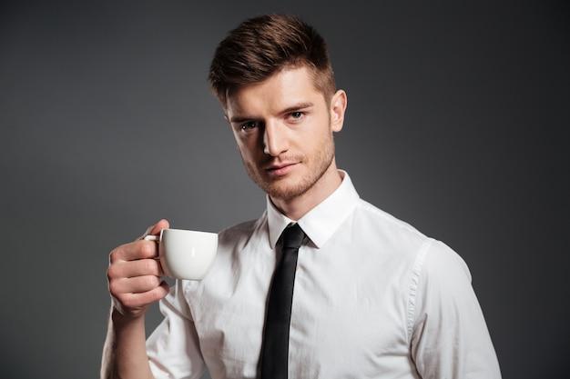 Portret van een knappe jonge zakenman met kop koffie