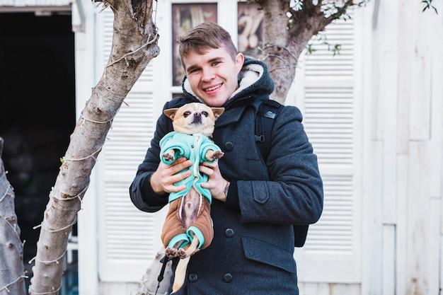 Portret van een knappe jongeman die een schattige chihuahuahond buiten vasthoudt