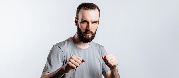 Portret van een knappe jongeman die fronst terwijl hij naar de camera kijkt die vuisten vasthoudt en bokst op een witte achtergrond met ruimte voor reclame mock-up