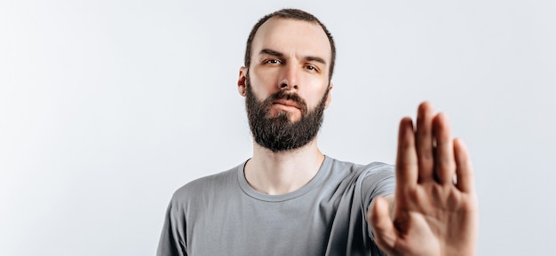 Portret van een knappe jongeman die fronst terwijl hij naar de camera kijkt en de hand tegenover hem vasthoudt en stopgebaar zegt op een witte achtergrond met ruimte voor een advertentiemodel