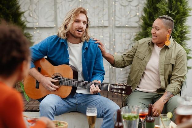 Portret van een knappe jongeman die gitaar speelt en zingt terwijl hij geniet van een buitenfeest met vrienden, kopieer ruimte