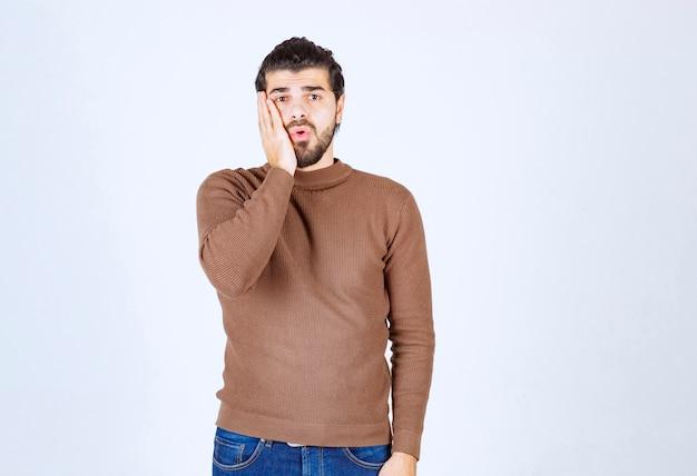 Portret van een knappe jongeman in een casual trui met palm in de buurt van de wang.