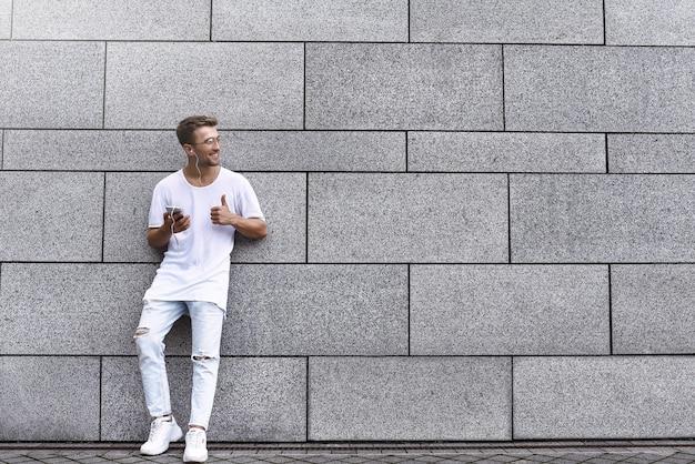 Portret van een knappe jongeman in vrijetijdskleding die geniet van muziek op je mobiele telefoon, tegen een bakstenen muur. kopieer ruimte