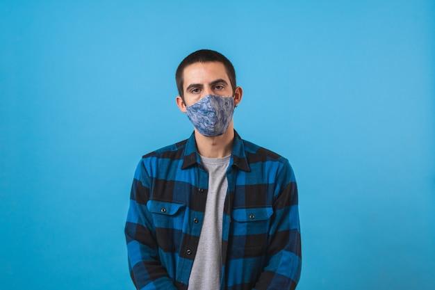 Portret van een knappe jongeman met een chirurgisch medisch masker die naar de camera kijkt