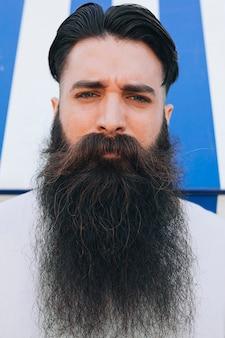 Portret van een knappe jongeman met lange baard camera kijken