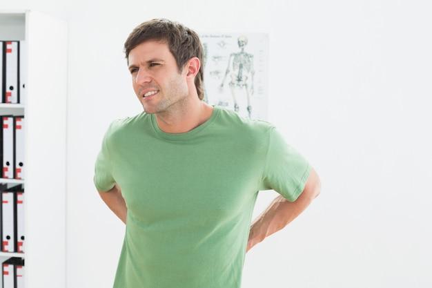 Portret van een knappe jongeman met pijn in de onderrug