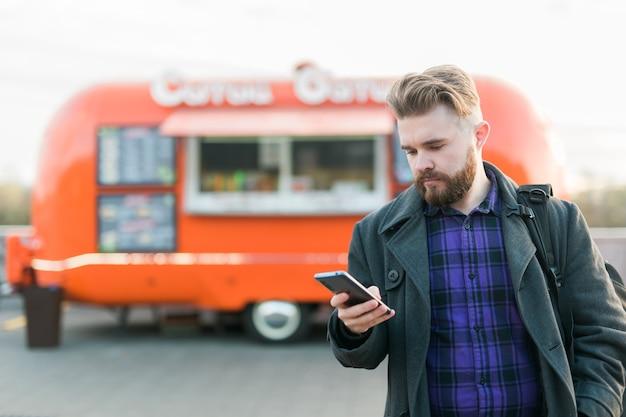 Portret van een knappe jongeman met smartphone die voor een foodtruck staat
