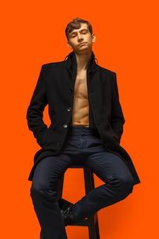 Portret van een knappe jongeman op oranje muur