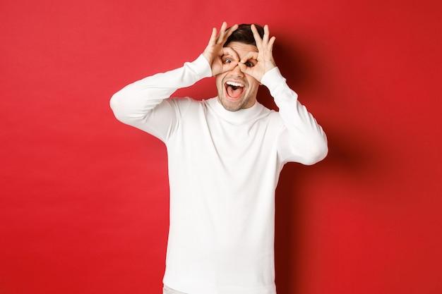 Portret van een knappe jongen in een witte trui die een grappig masker maakt met vingers die er gelukkig uitzien en glimlachen