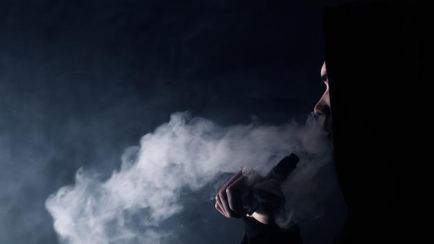 Portret van een knappe jongen in een zwarte hoed en zonnebril die een dampwolk van een e-sigaret vapen en uitademt