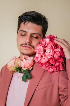 Portret van een knappe jongen met dichte ogen. knappe jongeman met bloemen om zijn nek en naast zijn gezicht, gekleed in een roze pak