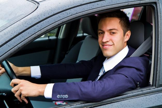 Portret van een knappe kerel die zijn auto drijft