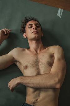 Portret van een knappe krullende man met naakte torso liggend op de groene vloer
