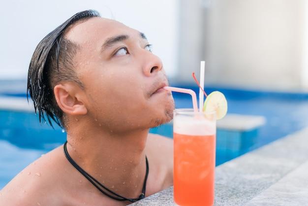 Portret van een knappe man die aan de rand van een zwembad rust