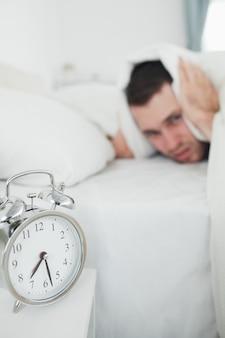 Portret van een knappe man die betrekking hebben op zijn oren, terwijl zijn wekker rinkelt