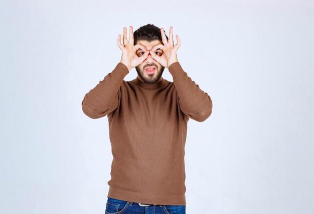 Portret van een knappe man die door de vingers kijkt