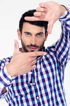 Portret van een knappe man die frame met vingers toont en voorzijde bekijkt die op een witte muur wordt geïsoleerd