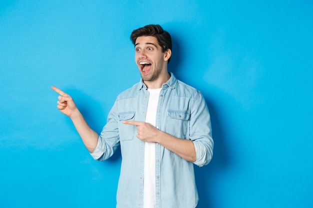 Portret van een knappe man die kijkt en met zijn vingers naar links wijst van opwinding, staande tegen een blauwe achtergrond.