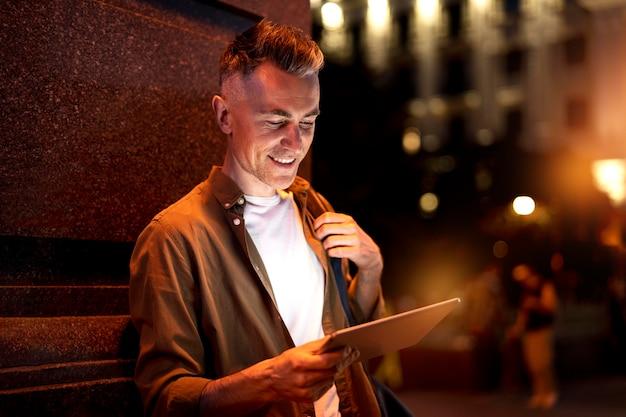Portret van een knappe man die 's nachts een tablet gebruikt in de stadslichten