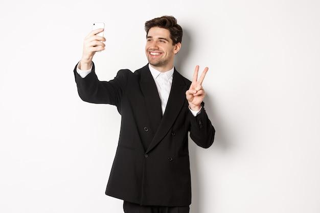 Portret van een knappe man die selfie neemt op nieuwjaarsfeest, pak draagt, foto neemt op smartphone en vredesteken toont, staande tegen een witte achtergrond.