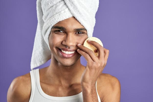 Portret van een knappe man die zijn gezicht schoonmaakt en naar een camera kijkt met cosmetische pads op een paarse achtergrond