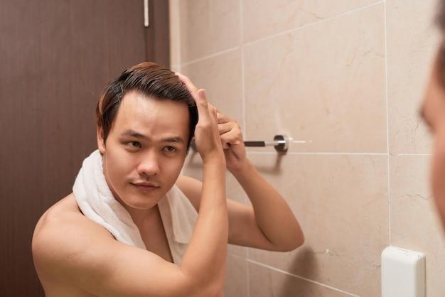 Portret van een knappe man die zijn haar in de badkamer borstelt.