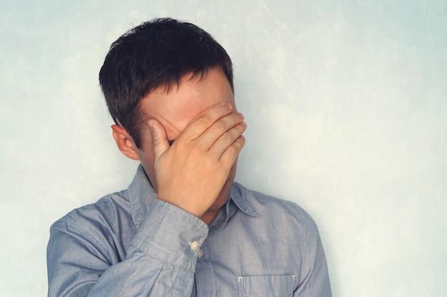 Portret van een knappe man die zijn ogen bedekt met handen geïsoleerd op een witte achtergrond, een jonge man in een blauw shirt houdt zijn hoofd vast. het begrip vermoeidheid. sluit je ogen voor het probleem.