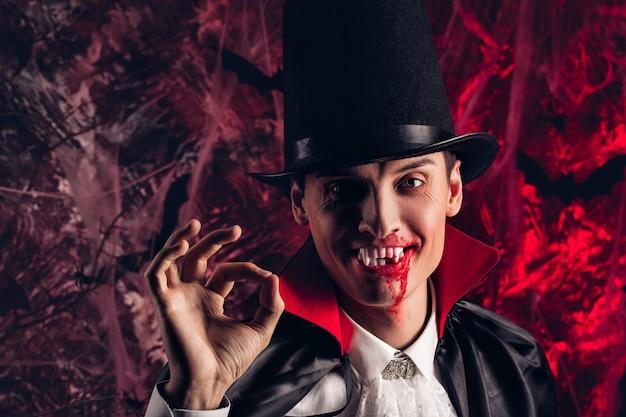 Portret van een knappe man gekleed in een dracula-kostuum voor halloween. lachende vampier