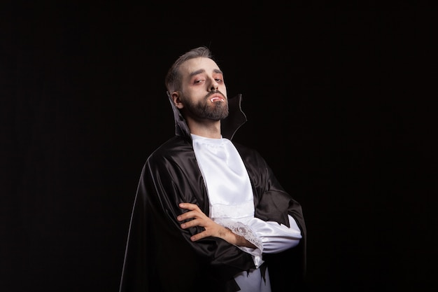 Portret van een knappe man gekleed in een dracula-kostuum voor halloween. vampier tanden. enge demon.