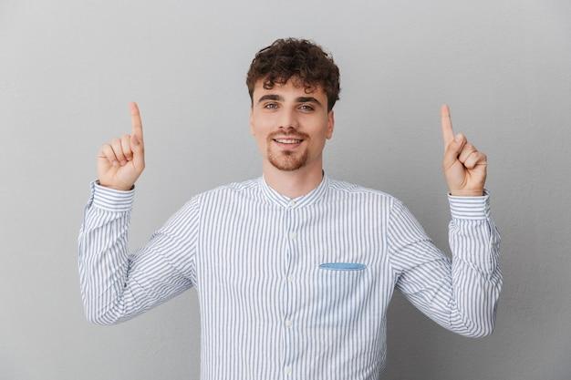 Portret van een knappe man gekleed in een shirt glimlachend en met de vingers naar boven wijzend naar copyspace geïsoleerd over grijze muur