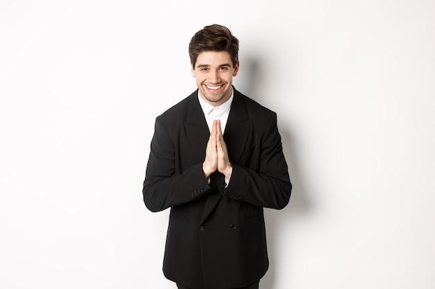 Portret van een knappe man in een zwart pak, dankbaar, bedankt en beleefd buigend, glimlachend als hand in hand, dankbaarheid uitdrukkend, staande op een witte achtergrond