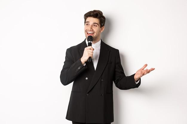 Portret van een knappe man in een zwart pak die een lied zingt, een microfoon vasthoudt en een toespraak houdt, staande tegen een witte achtergrond