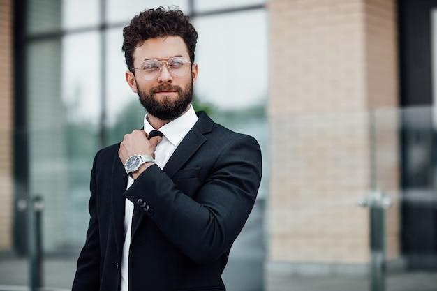 Portret van een knappe man in een zwart pak met een horloge aan zijn hand