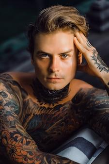 Portret van een knappe man in tatoeages