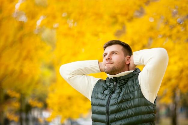 Portret van een knappe man met de handen achter zijn hoofd in een herfst park