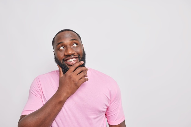 Portret van een knappe man met een brede glimlach houdt de kin gefocust boven, gekleed in een casual roze t-shirt geïsoleerd over een witte muur