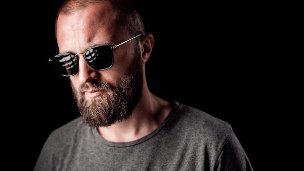 Portret van een knappe man met een lange, goed in orde gemaakte baard die zonnebril en grijs overhemd draagt