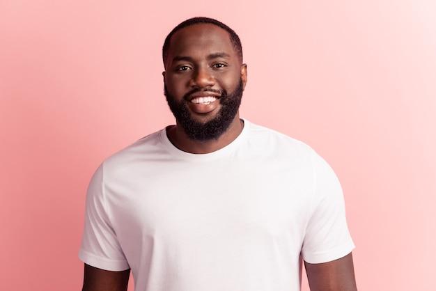 Portret van een knappe man met een positieve blik camera die een glanzende glimlach op de roze muur straalt