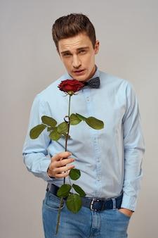 Portret van een knappe man met een rode roos als een geschenk in zijn handen