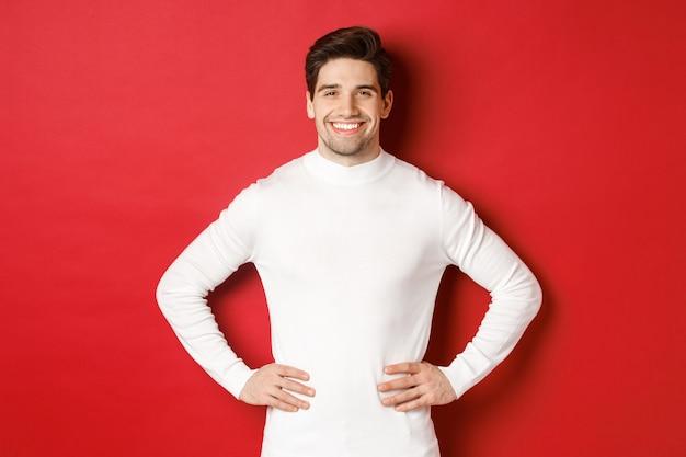 Portret van een knappe man met haren, witte trui dragend, glimlachend en zelfverzekerd, staande tegen een rode achtergrond. concept van nieuwjaar en wintervakantie.