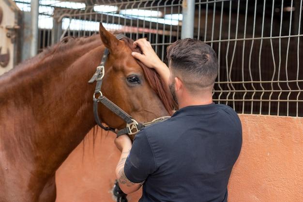 Portret van een knappe man met zijn paard staande op de stal