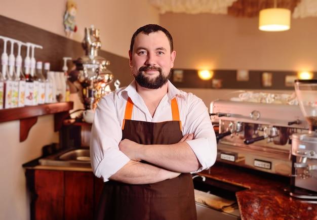 Portret van een knappe mannelijke barista in een schort